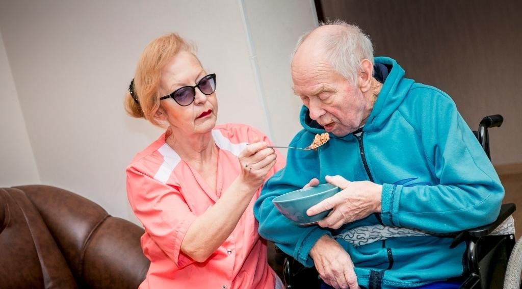 Женщина кормит старика