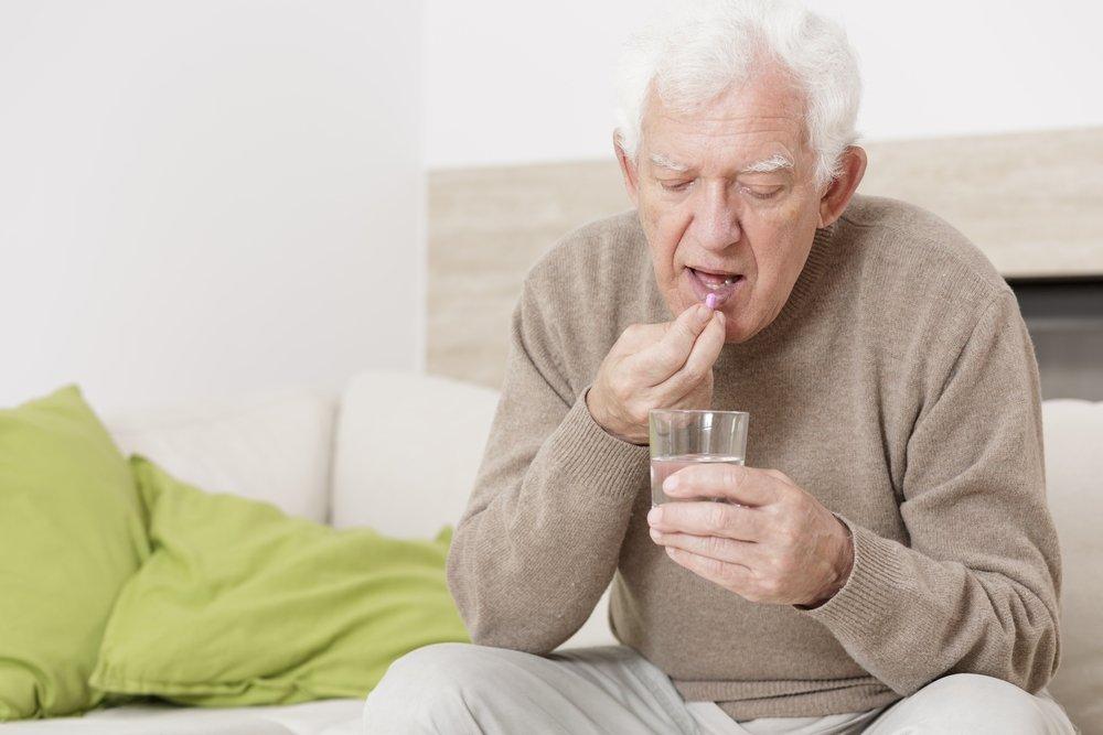 Старик пьет таблетки