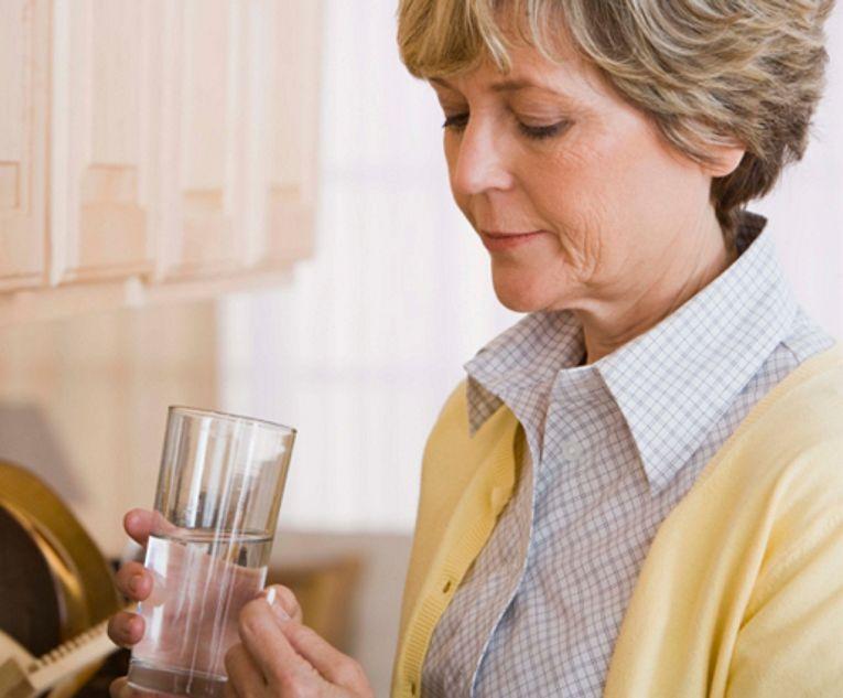 Вода и таблетка в руках женщины