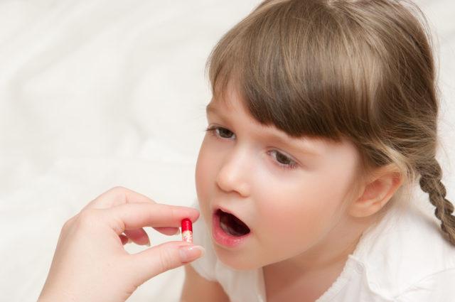 Девочке дают таблетку