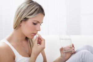 Девушка держит таблетку и воду