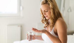 Девушка держит воду и таблетку