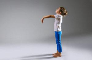 Девочка стоит с вытянутыми руками