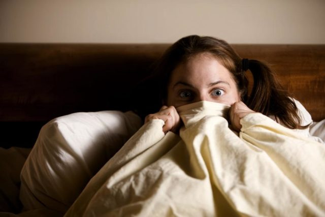 Девушка закрыло лицо одеялом