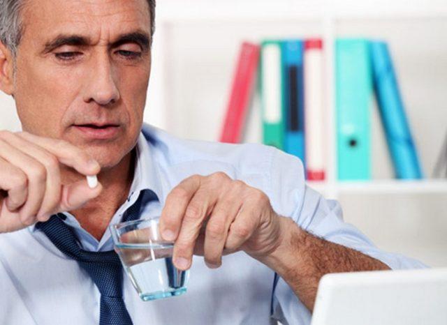 Мужчина держит воду и таблетку