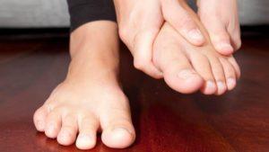 Девушка держит ногу