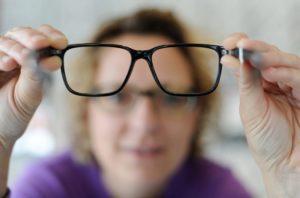 Женщина держит очки