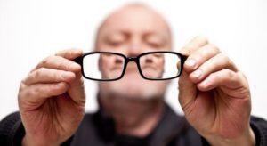 Мужчина держит очки