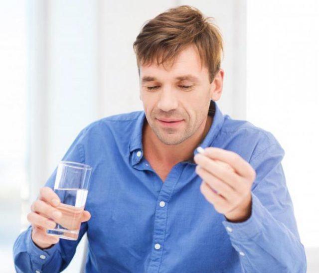Мужчина держит таблетку и воду