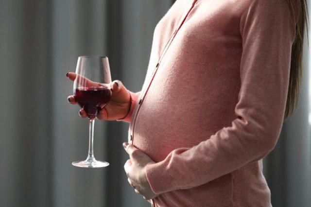 Беременная пьет вино