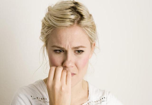Женщина держит руку у рта