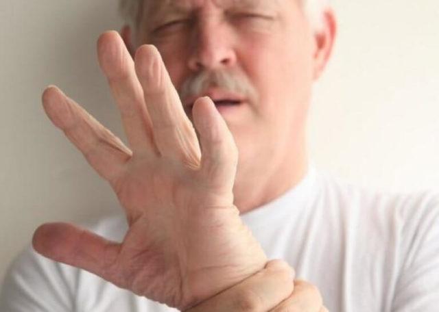 Мужчина держит руку