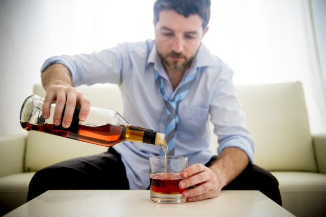 Мужчина держит бутылку