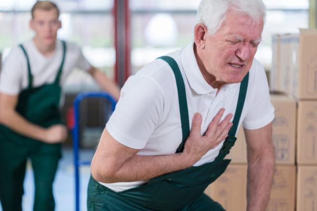 Пожилой мужчина держится за сердце